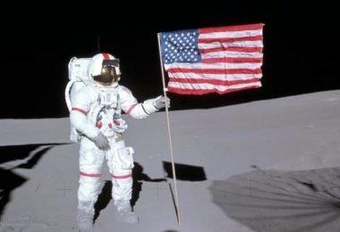 Alan Shepard segura a bandeira americana na Lua